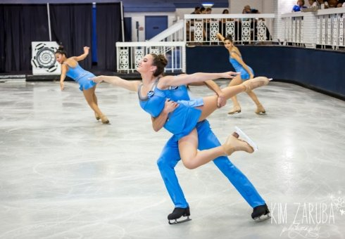 people ice skating in blue outfits