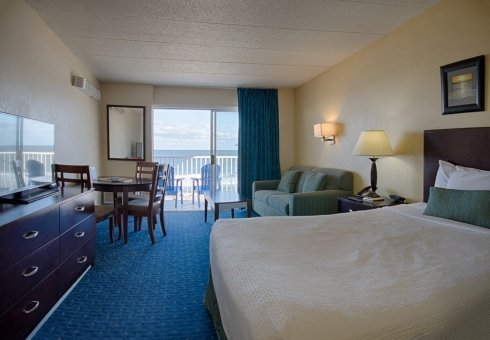 king bed hotel room with oceanfront balcony